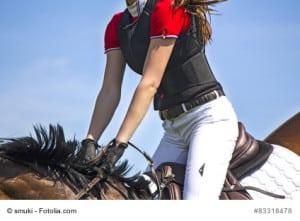 Diese Dame trägt eine Reitweste zu Ihrer eigenen Sicherheit. Immer mehr Frauen reiten heute auf Nummer Sicher.